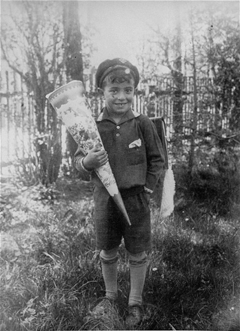 Photograph of schoolboy holding a large paper cone